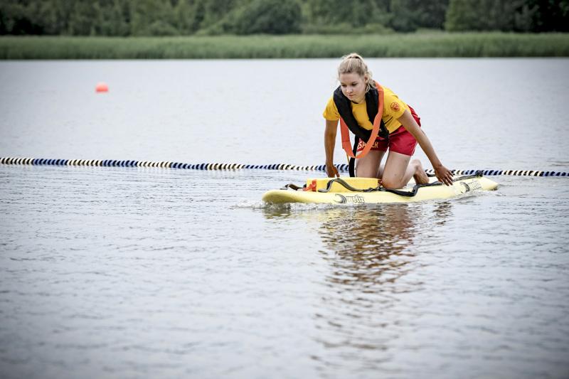 Alexandra Pihlajamäki harjoittelee hiljaisena päivänä pelastusvälineiden käyttöä kesätyöpaikallaan Ispoisten uimarannalla Turussa.