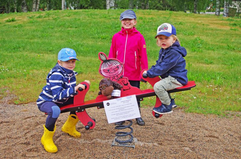 Lupsunmutkan leikkikentällä Niilo, Jenni ja Saku Mehtälä ja sateessa kastunut gorilla.