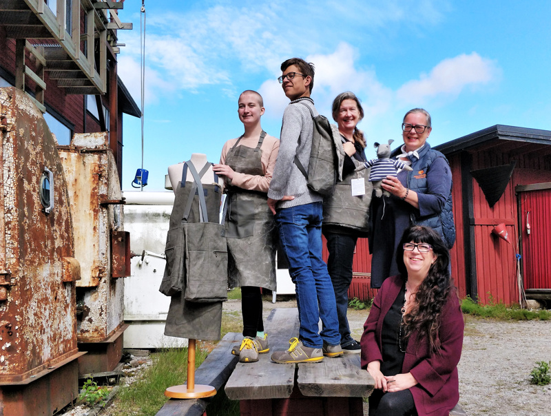 Kesätyöntekijät Roosa Ylinampa ja Arnold Sågfors sekä koordinaattori Marie Ahlin ja Maria Lunabba Vega-säätiöstä esittelevät muotisuunnittelija Janet Lönnqvistin Vegan vanhoista purjeista valmistamia tuotteita essusta laukkuihin.