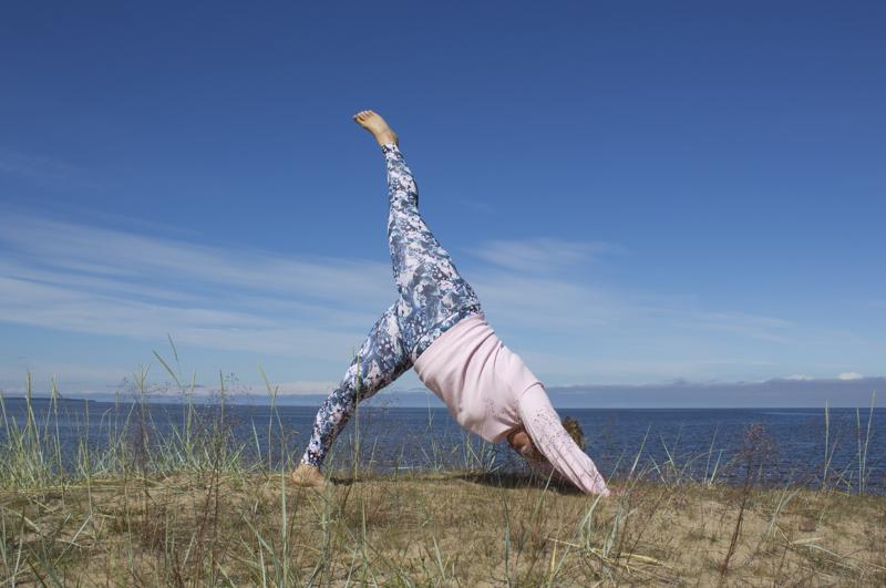Katriina Pohjoiskangas tekee Kalajoella rantajoogaa. Kuvan jooga-asana eli asento on alaspäin katsova koira.