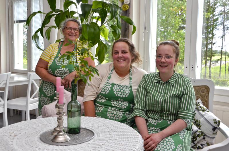 Eija Kupari (vas.), Jenni Hilliaho ja Ida Kupari pyörittävät kahvilaa muiden työntekijöiden kanssa kauniissa maalaisympäristössä.