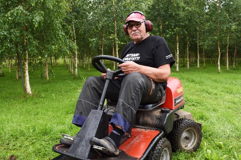 Esko Törmälehto on asunut koko ikänsä Törminperällä Virtalassa, mutta työ ajohommissa piti miestä liikkeellä liki 40 vuotta. Eläkkeellä Esko on siirtynyt pienemmän menopelin rattiin, jolla hän pitää heinikot kurissa taustalla näkyvässä omassa puutarhassaan.