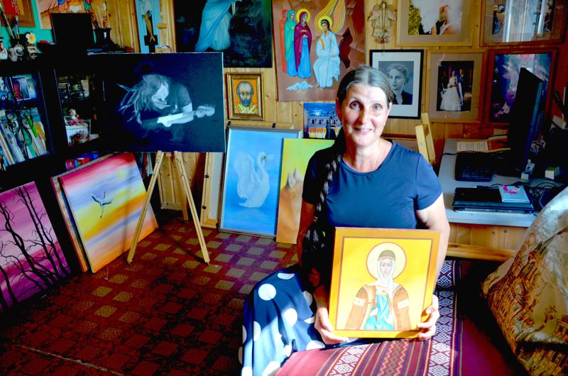 Olga Melet-Pajuojan työhuoneessa on valmiita töitä luontoaiheista ja maisemista ikoneihin. Melet-Pajuojalla on sylissään maalaamansa ikoni suojeluspyhimys Olgasta.