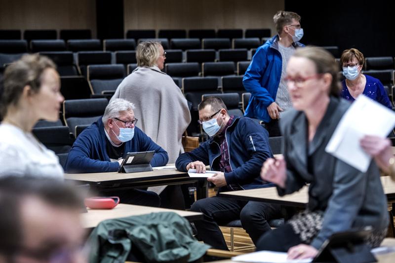 Kokkolan kaupunginvaltuutettu korona ryydittämässä kevään kokouksessa. Etualalla Johanna Paloranta (kesk.) ja Sirpa Orjala (sd.) Kokkolan valtuuston kokouksessa.