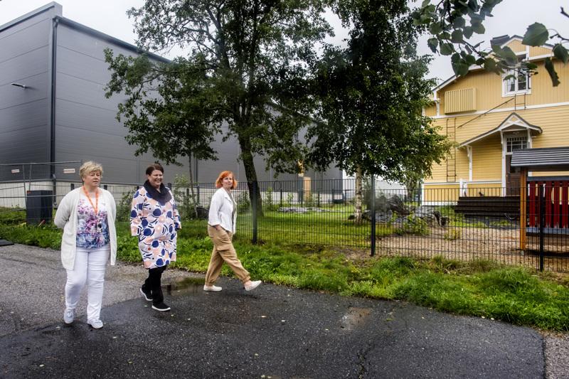 Kaupunginjohtaja Stina Mattila, kaupunkiympäristöjohtaja Nina Kujala ja kaupunkilupapäällikkö Minna Väisänen Falanderinkadulla. Taustalla Keltaviirin päiväkoti ja paloaseman uusi kalustohalli.
