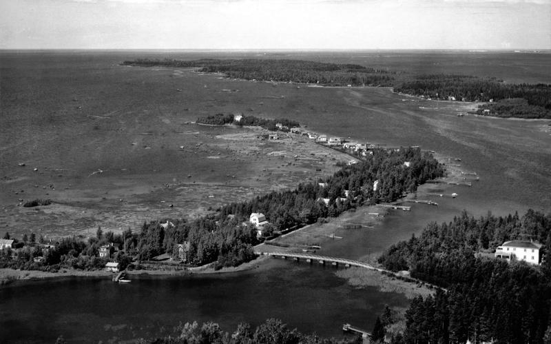 """Kuva Morsiussaaresta vuodelta 1953. Kuvassa oikealla Soldatskär. Ensimmäinen talo sillan jälkeen vasemmalla on Morsiussaarentie 1, saaren itärannalla näkyy huviloiden ja rantaviivan välissä kulkenut """"pikkutie""""."""