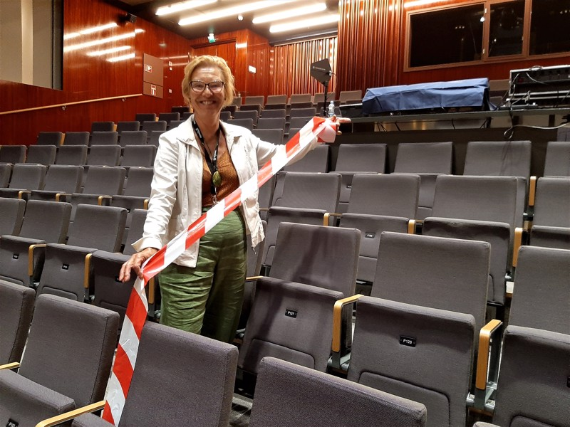 Schauman-sali jaetaan keskeltä kahtia, ja toistaiseksi vain puolet istumapaikoista on myynnissä. Lise Strand sovittelee jo eristysnauhaa paikoilleen.