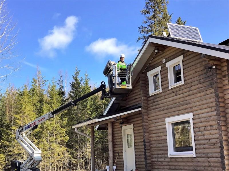 Maalari joutuu usein nousemaan korkeuksiin. Kuvassa Jari Sandkvist maalaa Kärsämäellä metsästysseuran mökkiä.