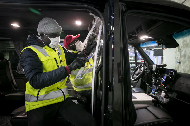 Tampereen Aluetaksi on koronasuojannut taksejaan. Newjob yrityksen asentajat Bubacarr Konateh Dukureh (pun. lippis) ja Ebrima Toyray asensivat suojakalvoa taksiin matkustamon ja kuljettajan väliin.