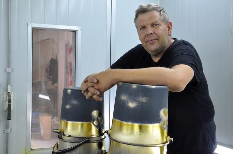 Janne Hautakoski käytti muoviämpäreitä maalausjalustoina hänen työstäessään tilausta urheilujoukkueelle, joka halusi kullan kiiltoa kypärien pintaan.