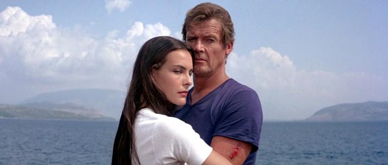 Sinun silmiesi tähden. Roger Moore, 53, ei saa pidettyä turvaväliä Carole Bouquet'hen, 23, Bond -elokuvassa Erittäin salainen.