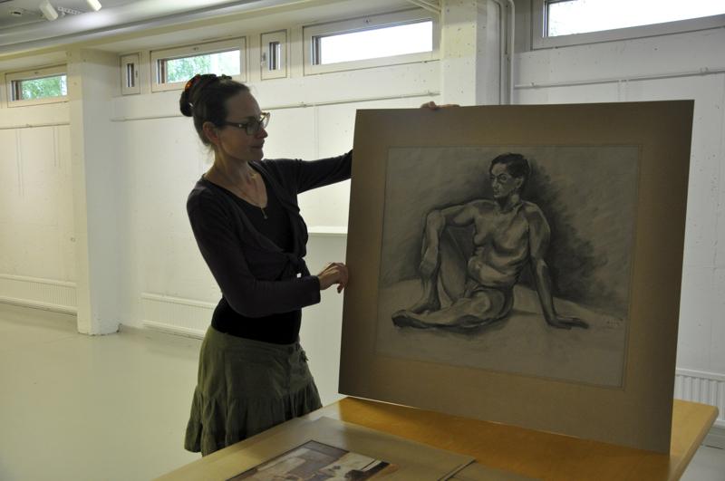 Maria Markkio näyttää Tom Tiaisen Istuva mies -hiiliteosta.