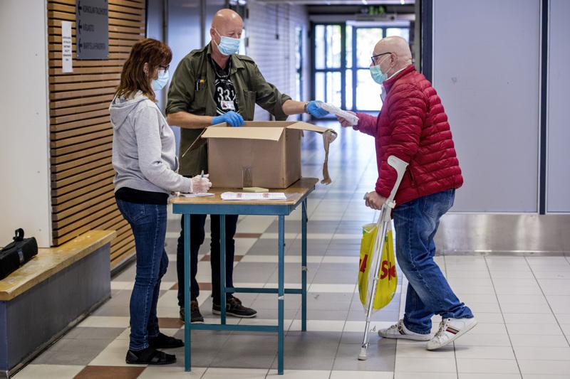 Perhetyöntekijä Kristiina Haapaniemi ja aikuissosiaalityöstä ja asumisneuvonnasta vastaava Bo-Göran Heinola jakavat maskeja Seppo Liedekselle.