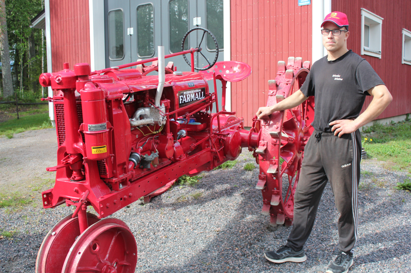 """Farmall-traktoreiden valmistus alkoi vuonna 1924. Mustolan Farmall on vuodelta 1937. Taustalla halli, jossa Mustola traktoreidensa kanssa """"talostelee""""."""
