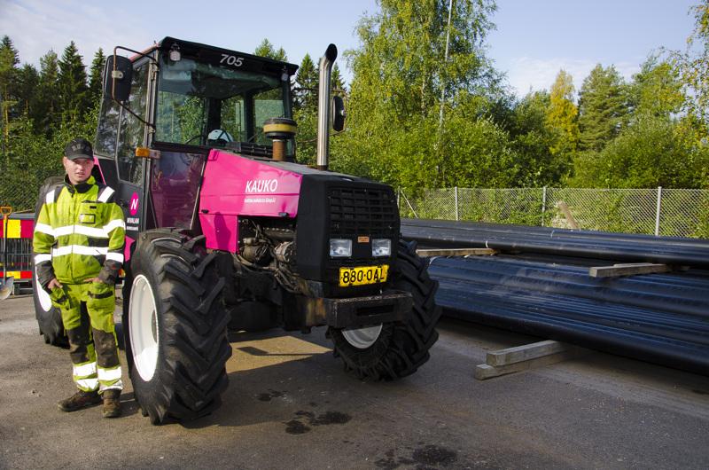 Kaukolämmmön traktori on teipattu yhtiön väreillä. Sillä kuljetetaan lämpöputkia ja pieniä maakuormia. Putkien kuormaus on tuttua puuhaa työharjoittelussa olevalle Joni Hosionaholle. Hän opiskelee toista vuotta ammattiopiston putkipuolella.