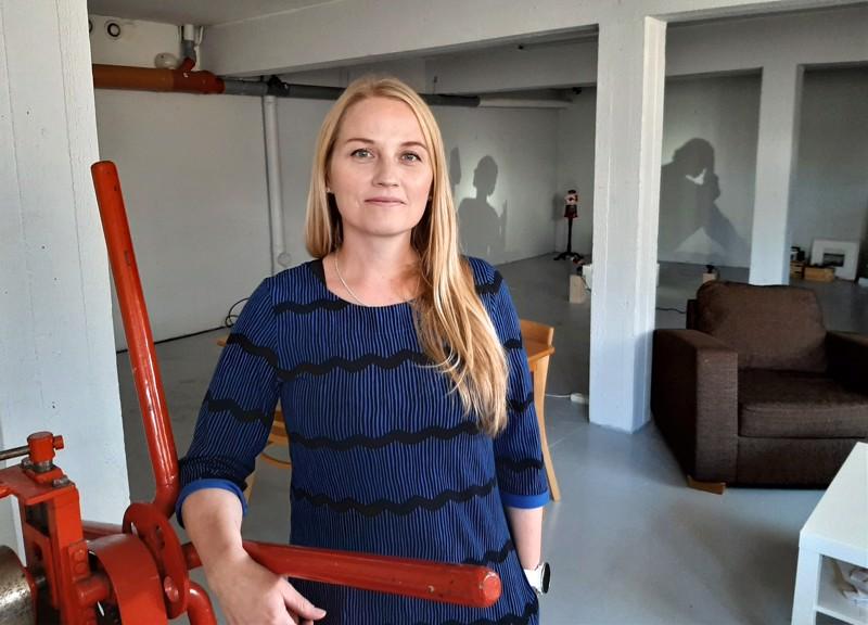 """Anni Laukka työhuoneessaan, jonka hän hankki  lopputyönäyttelyään varten viime keväänä.  Taustalla lopputyönäyttelyyn sydämistä ja peukuista rakennettu veistosvarjoteos """"Hearts & Thumbs"""", joka luo kaksi erilaista varjoa."""