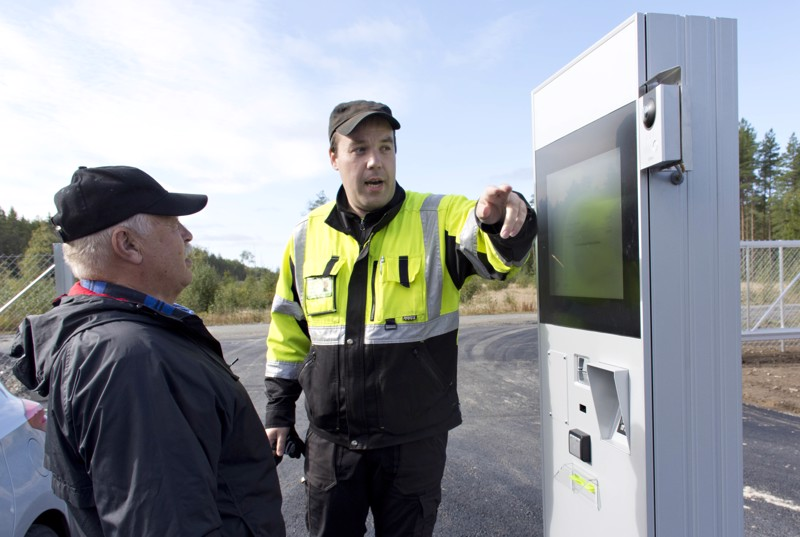 Vestian Jouni Rautionaho opasti kalajokista Seppo Löllöä automaatin käytössä.