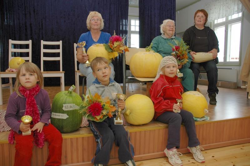 Sylvi Nevala (ylärivissä keskellä) oli vienyt Ainalin kurpitsakilpailun voiton 16 kilon möhkäleellä, jonka hän oli kasvattanut keittiökompostissa Säynäjäniemessä.