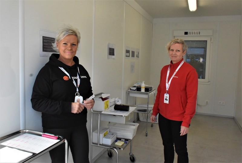 Näytteet otetaan parkkipaikalle sijoitetun kontin edustalla auton ikkunasta. Konttia esittelevät Pihlajalinnan Pietarsaaren palveluvastaava Monica Björklund ja Pohjanmaan palvelupäällikkö Jaana Perälä-Haapa-aho.