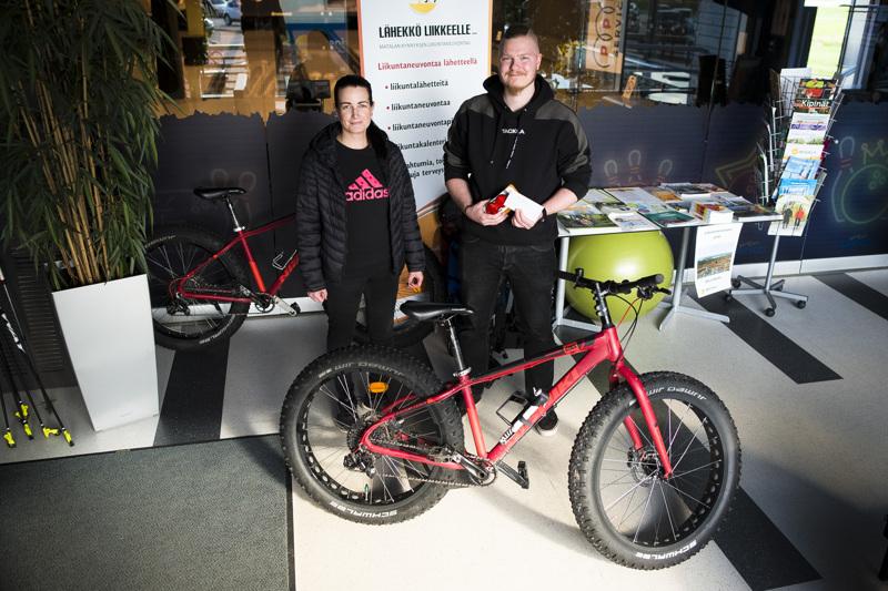 Henri Heiska luovutti Sanna Södergårdille pyöräilykampanjan pääpalkinnot: pyörälahjakortin sekä uuden tieliikennelain mukaiset etu- ja takavalon. Kuvassa myös Uikosta vuokrattavana oleva läskipyörä, jollainen on yksi vaihtoehto myös Södergårdin uudeksi pyöräksi.