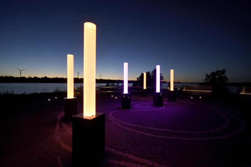 Meripuiston valotaideteos hehkuu illan hämärtyessä eri väreissä.