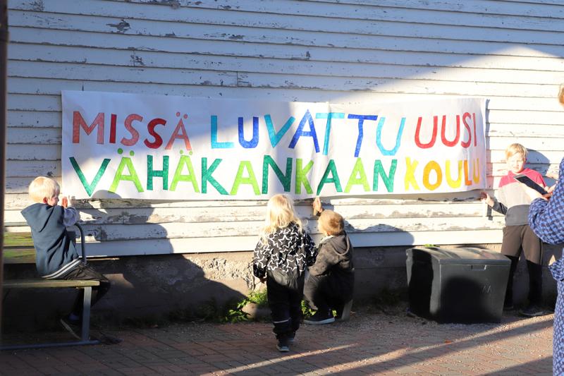 Lasten tekemät banderollit kertovat viestiä uuden koulun puolesta, joka on luvattu jo heidän vanhemmilleen.