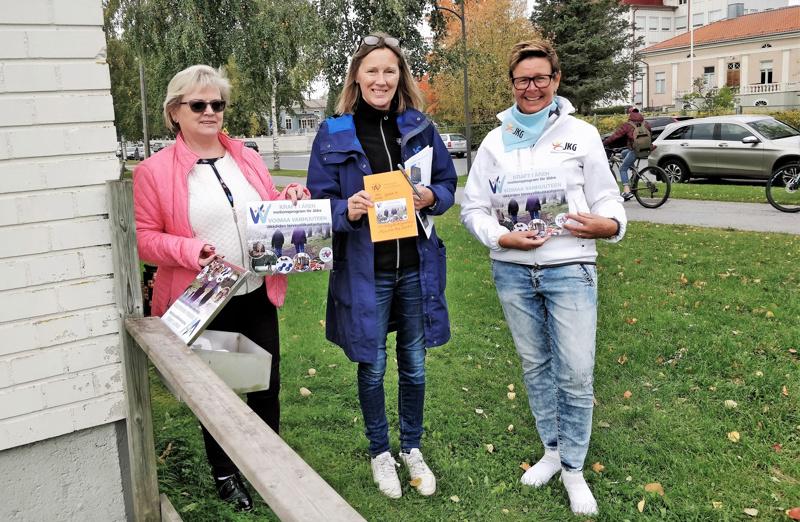 """Ylös, ulos ja lenkille omaan tahtiin,  kannustavat Voimaa vanhuuteen -työryhmän jäsenet liikuntatoimenjohtaja Tove Jansson, erityisliikunnanohjaaja Marja Eriksson ja Solveig """"Soli"""" Granholm voimisteluseura JKG:stä. Puutarhakadun 75+ -kuntolaatikolla on riittänyt kävijöitä."""