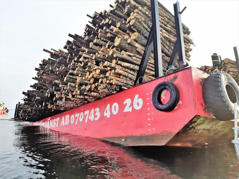 Hinaaja Röjvikin puoliksi uponneesta proomusta on tippunut suuria määriä puuta mereen Pietarsaaren edustalla.