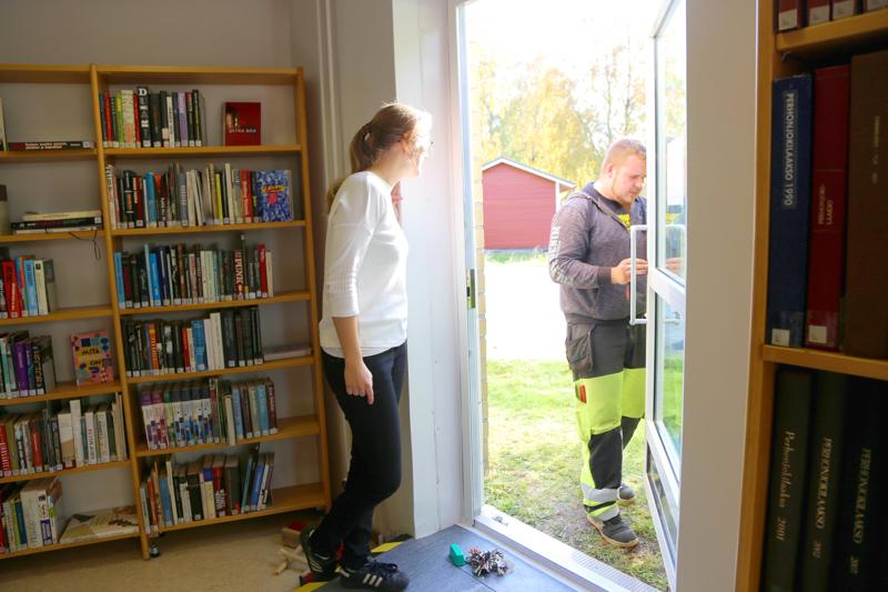 Kirjastossa työskentelevä Maria Nikula seuraa, kun kiinteistöhoitaja Markus Harjukoski korjaa hätäuloskäynnin rikottua sähkölukkoa. Tällä kertaa lukko saatiin kuitenkin kuntoon.
