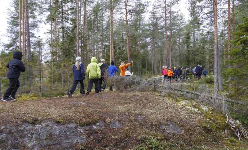 Koululaiset kulkivat jonossa luokittain kohti metsäkirkkoa.