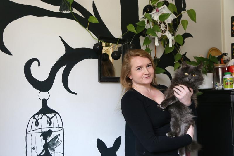 Nita Nurminen ja Miska-kissa. Kodin mustia yksityiskohtia ryydittävät värikkäät sisustusesineet, joita Nita on haalinut kirppareilta.