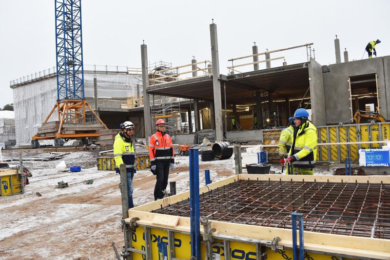 Koulun rakentaminen on edistynyt kolmessa kuukaudessa kovaa vauhtia. Rakennusliiton puheenjohtaja Matti Harjuniemi (kuvassa keskellä) kiersi keskiviikkona työmaalla jututtamassa työntekijöitä.