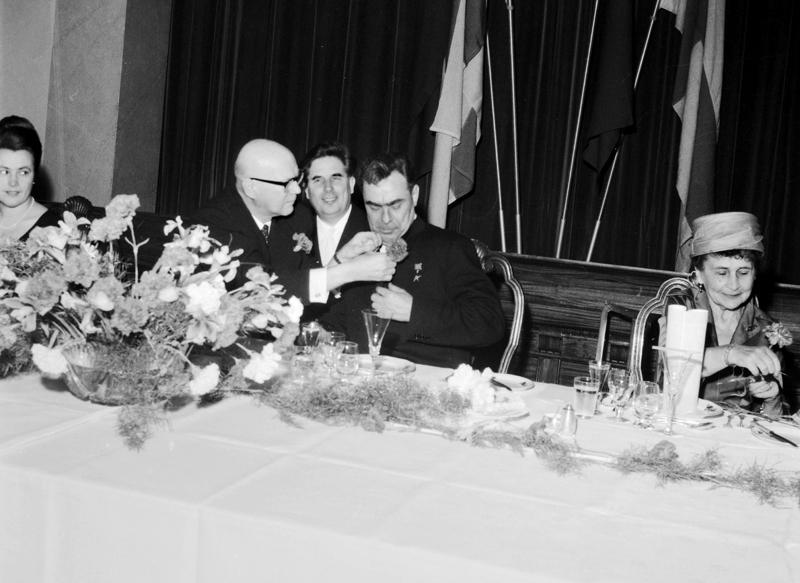 Presidentti Urho Kekkonen kiinnittää neilikkaa Neuvostoliiton presidentin Leonid Brežnevin rintaan juhlalounaalla syksyllä 1961. Oikealla Sylvi Kekkonen. Kuva: Kauko Kanerva / Museovirasto.