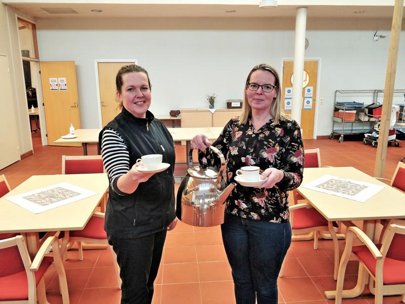 Emäntä Katja Siltamäki ja johtava emäntä Maarit Sauna-aho esittelevät kultareunaisia kahvikuppeja ja 10 litran kahvipannua, jotka kuuluvat huutokaupattavien astioiden joukkoon.