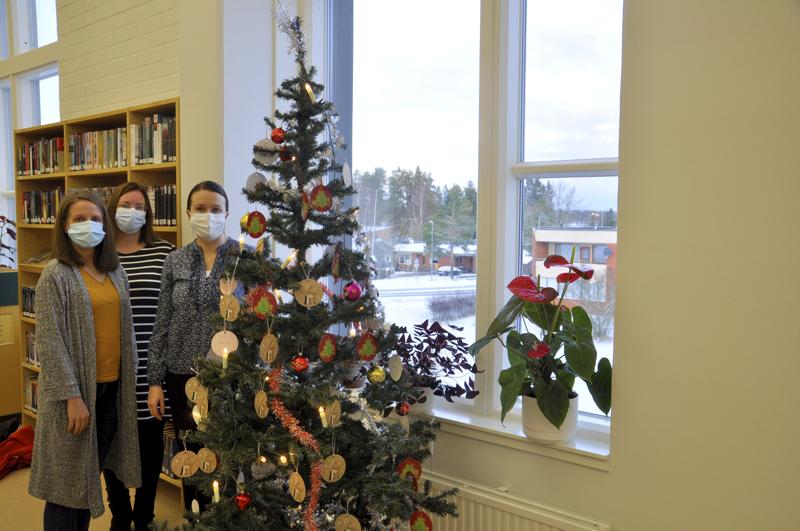 Toholammin joulupuu. Tiina Keskisipilä, Anniina Lintilä ja Anu Ahokas toivat pakettikortteja Joulupuu-keräyksen kuuseen Toholammin kirjastoon.