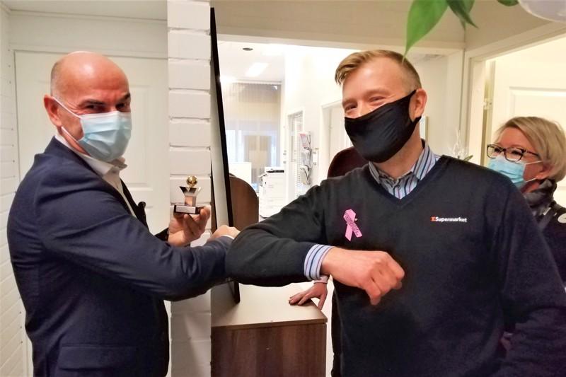 Jan Riska (vasemmalla) vastaanotti yrittäjäpalkinnon Aki Salmiselta. Taustalla oikealla yrittäjäyhdistyksen voimahahmoihin kuuluva Jaana Ilmonen.