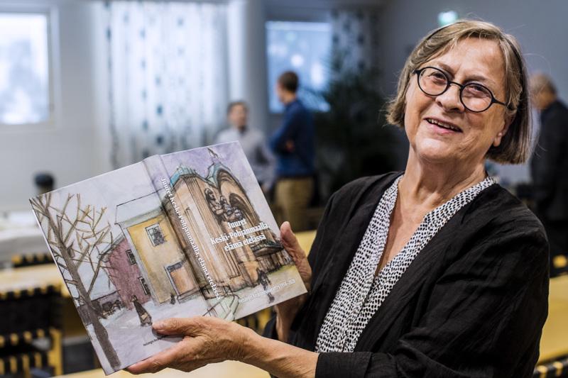 Eila Rekilä esittelee teoksen kantta, jonka on taiteillut kokkolalaislähtöinen kuvataiteilija Tero Annanolli.