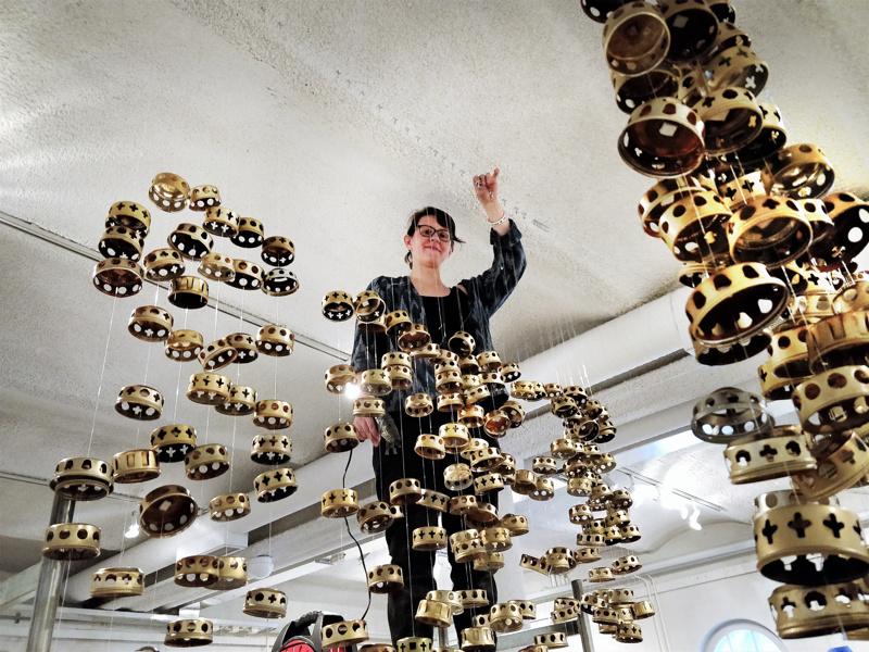 Emma Ahlgren ripustamassa 900:sta hautakynttilän kannesta koostuvaa teostaan Memento mori Memento vida.