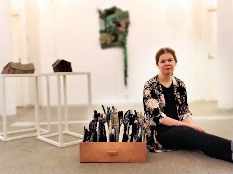 """Sara Sundqvist ja laatikossa ompeluteos """"Familjen""""."""