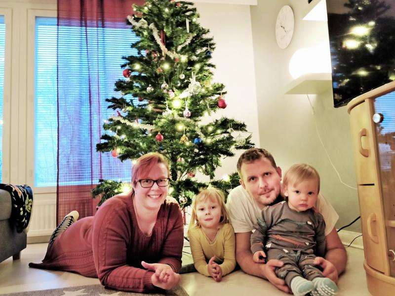 Pulkkisen perhe, Mira-äiti, Mimosa-tytär,  Jammu-iskä ja Paavo-poika tunnelmoimassa joulukuusen alla.