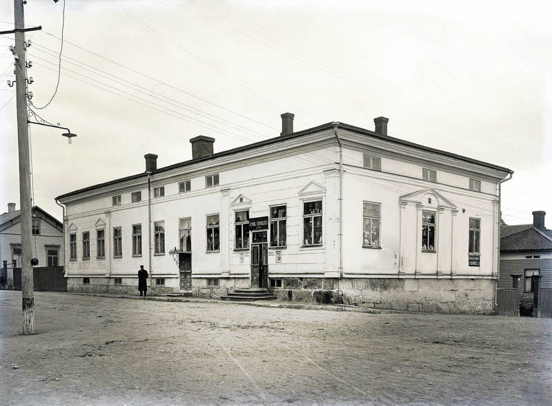 Kauppias Emil Simelius oli Pietarsaareen muutettuaan toiminut konttoristina Ph.U. Strengbergin palveluksessa. Vuonna 1897 hän osti Victor Nymanin kauppaliikkeen ja avasi kaupan Isokatu 10:ssä.