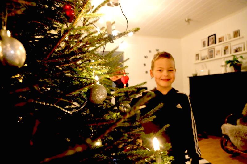 Noel ripusti eskarissa valmistamansa joulukoristeen hetki aikaisemmin sisään tuotuun kuuseen.