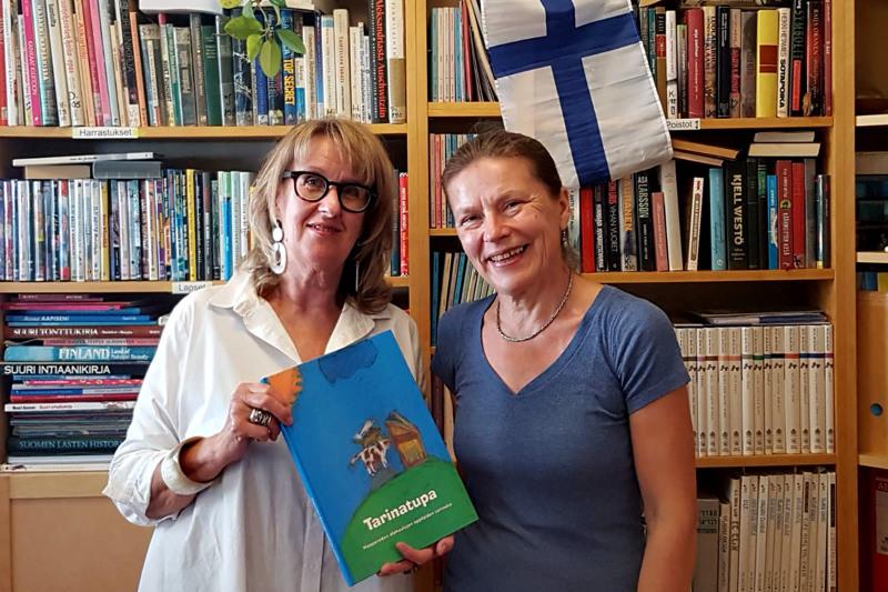 Kirjastonhoitaja Anu Morchy Levi (oikealla) otti ilolla vastaan Tarinatupa -kirjan, jonka Anneli Repo toi terveisinä Haapaveden kirjastolta Israelin Suomi-kirjastoon.
