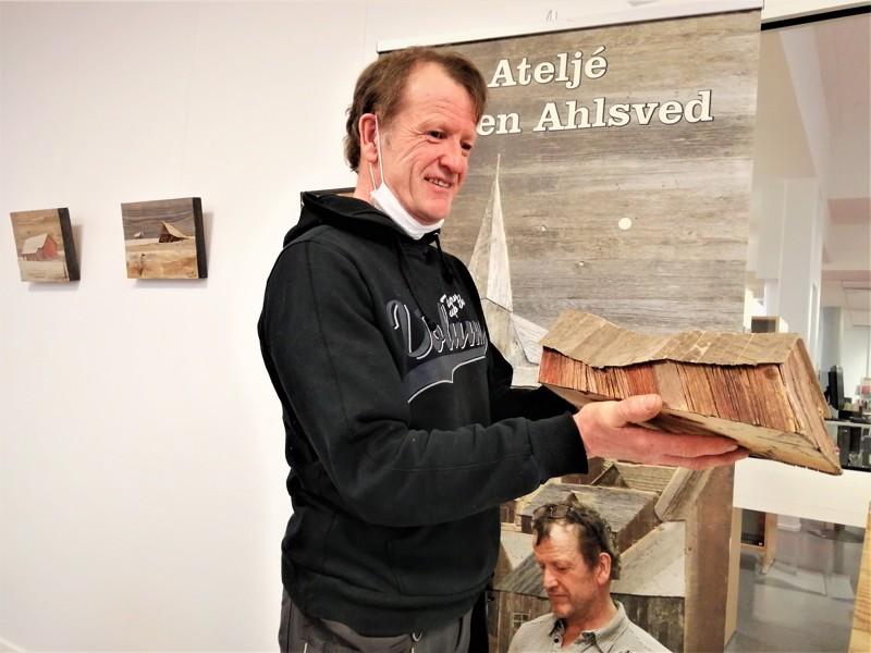 Taiteilija ja kättensä töinä syntynyt pienoismallilato.