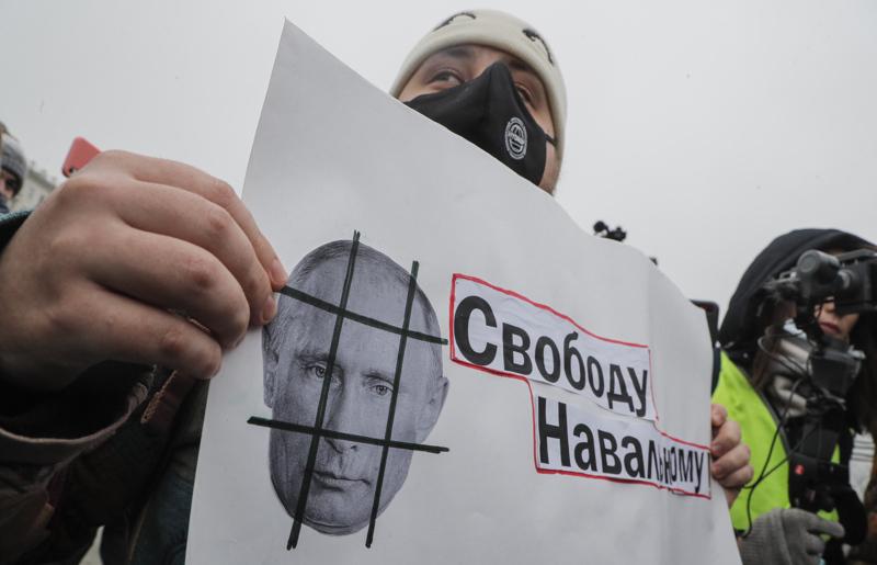 Protestoija pitelee lappua, jossa vaaditaan vapautta Navalnyille. Kaltereiden taakse toivotetaan puolestaan Putinia.