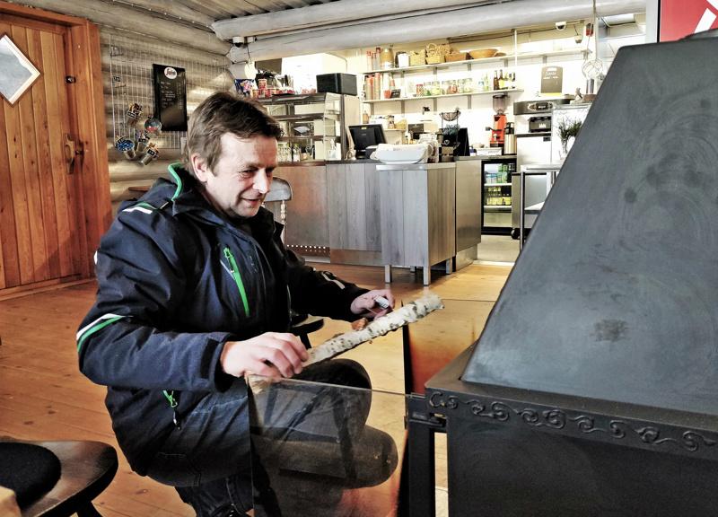 Pienemmässä kahvilasalissa on käytössä puukamiina, Sune Boström lämmityspuuhissa.