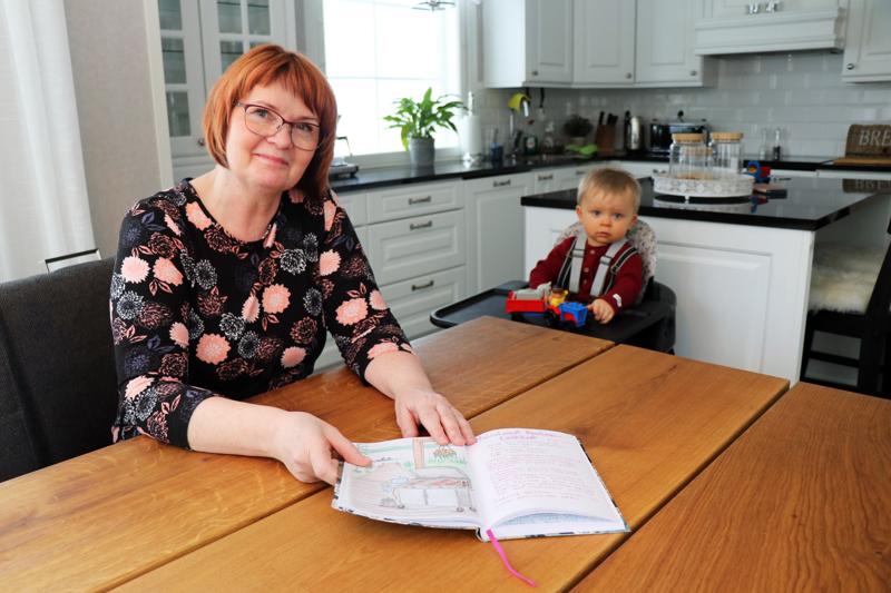 Tuija Kola on innostunut kokoamaan ja kuvittamaan yksiin kansiin arkireseptejä. Vieressä Jenna-tyttären Viljam-poika, jota Tuija-mummi hoitaa tämän talven .