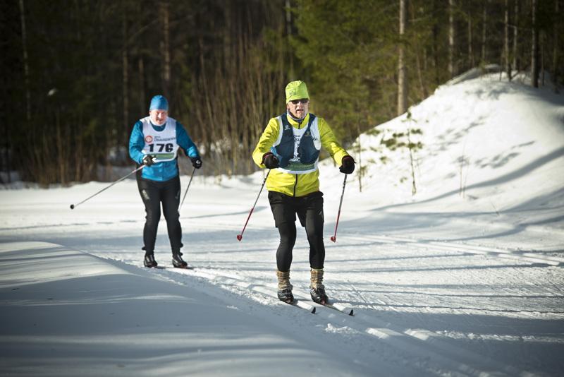 Hiihtohaasteen isät Onni Vähäaho (edessä) ja Arto Viitala taittoivat 100 kilometrin matkasta aimoannoksen yhtä matkaa. Puolimatkassa he pitivät lyhyen ruokatauon.