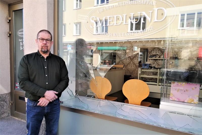 Smedlundin Kelloliikkeen yrittäjä Dick Smedlund ja näyteikkuna, jonka varas rikkoi kirveellä.