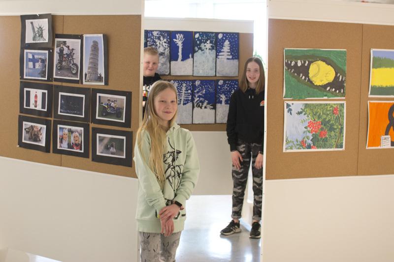 Lauri Malila (takana vas.), Elsa Korkiakoski ja Matleena Ohtamaa suunnittelivat kuvataidenäyttelyn teoksien järjestystä yhdessä opettajan kanssa.